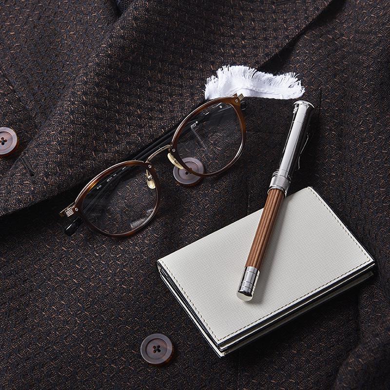 ジャケットのブラウンを基調に決めたら、小物は旬な茶系で揃えるのが吉。いたるパーツがリッチでコクまろなフォーナインズの「M-101」は、まさにその大代表です。全てが同系色では蒙昧な印象に陥りかねないため、コントラスト付けのために差したホワイトチーフを拾い、名刺入れにはヴァレクストラの白をチョイス。筆記具はファーバーカステルの鉛筆一筋、こだわりの強い嗜好性が垣間見られます。メガネは上と同じ、ペンシル4万5000円/ファーバーカステル(DKSHジャパン)、名刺入れ3万8000円/ヴァレクストラ(ヴァレクストラ・ジャパン)