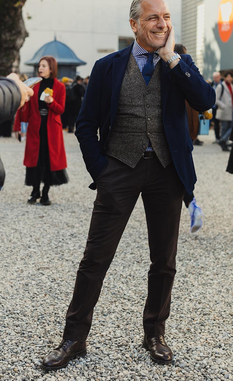 無地の紺ジャケットに黒パン、メダリオン入りの革靴を合わせた御仁。Vゾーンはギンガムチェクのシャツに無地のネイビータイと一見定番的ですが、貫禄ある大人にこそ、シャツはこんなチェックが効くのです。ロマンスグレイと呼応するような、グレー調のジレ(ベスト)もいい感じ。なによりこの笑顔が大人の余裕を物語ります。