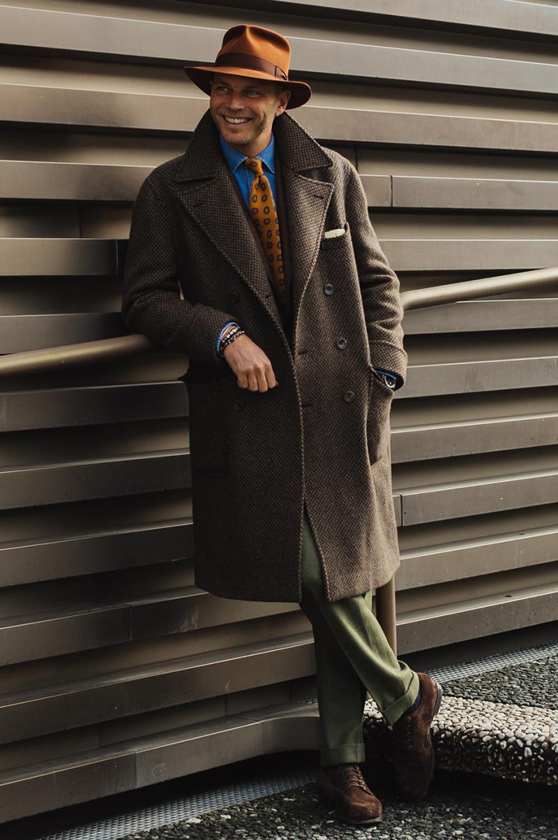 ナポリの老舗サルト、ルビナッチの3代目当主、ルカ・ルビナッチさんはスナップの常連。ブラウンのジャケットの上から同じくブラウンのコートをさらり。 襟元はダンガリーシャツにハットと同色のレンガ色の小紋タイを合わせ、鮮やかなコントラストを作っています。カジュアルなシャツもこんな色合わせで使うと、じつにシックなのです。