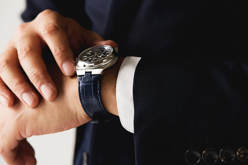 """オーヴァーシーズは、簡単にストラップの交換ができる""""インターチェンジャブル・システム""""を採用。そしてその恩恵を享受できるよう、全モデルがあらかじめ複数本のストラップをセットしています。ここではネイビーのアリゲーターストラップを装着し、よりスーツとの相性を高めています。"""