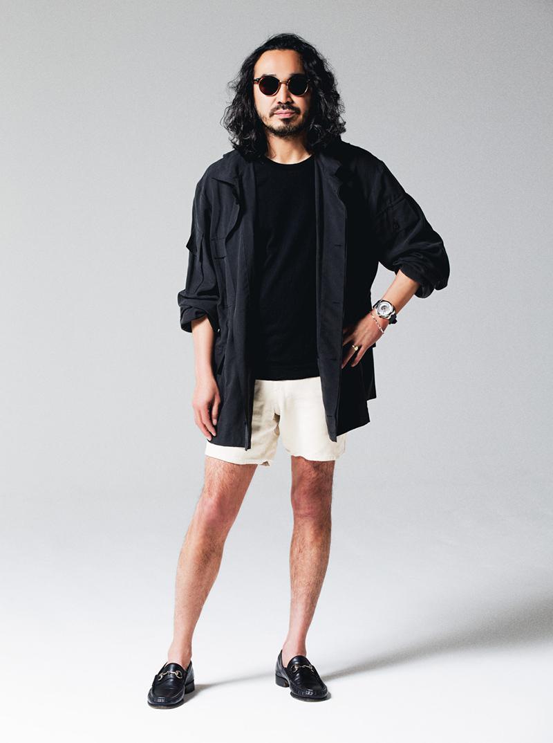 ミリタリー調デザインの黒シルクジャケットをゆるりと羽織り、下半身は白ショーツで軽快に。足元のビットローファー、そして何より腕のオーヴァーシーズの効果でとても大人っぽく、セクシーなショーツ姿となっています。