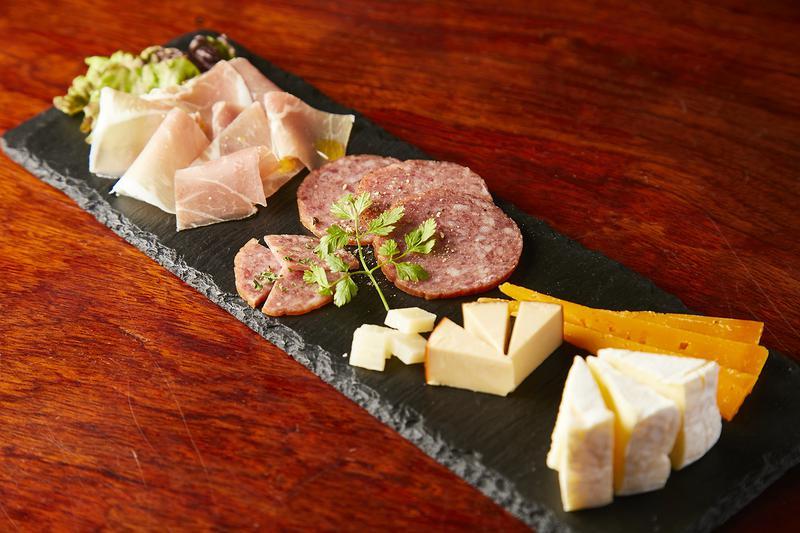 生ハムやサラミ、ミモレットやカマンベールチーズがひと皿にのった「盛り合わせ」1296円。