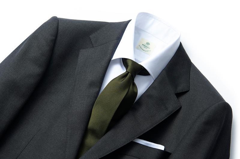 オリーブも今季のトレンドカラー。グリーン系は手強く感じるかもしれませんが、ダークな色調のオリーブなら写真のグレーをはじめ意外と幅広い色のスーツに馴染みます。ここではタイをコーデの主役にすべく、あえてプレーンな白シャツをチョイス。ストイックなコーデだからこそ、オリーブタイが大人の男の色気を示すさりげないポイントになっています。